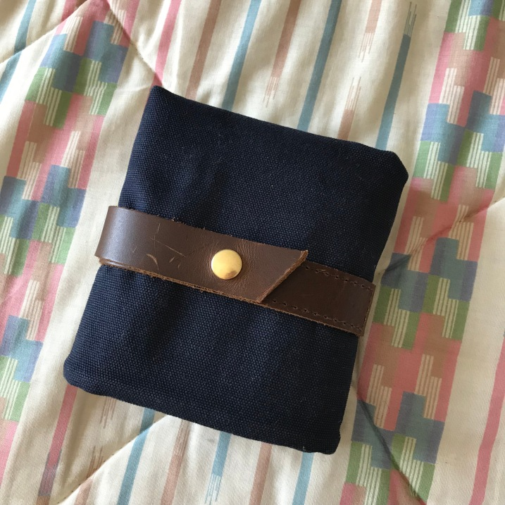 The needle case folds/rolls up nicely and is secured with a leather strap and brass snap-button.